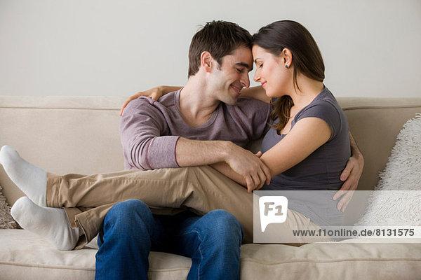 Paar auf Sofa  Frau sitzt auf dem Schoß des Mannes