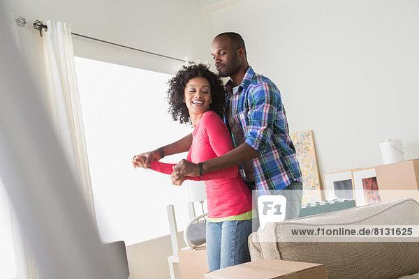 Mittleres erwachsenes Paar tanzt in neuem Zuhause