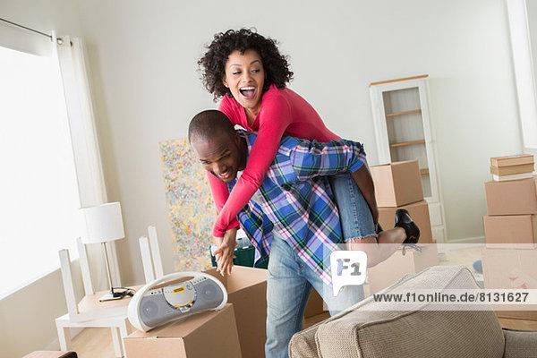 Mittleres erwachsenes Paar in neuem Zuhause  Mann gibt Frau Huckepack