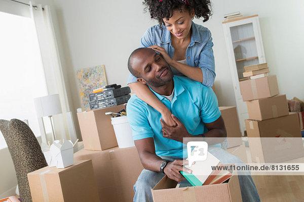 Mittleres erwachsenes Paar  das in ein neues Zuhause einzieht