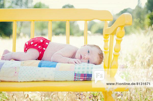 Neugeborenes Mädchen auf gelber Bank im Feld liegend