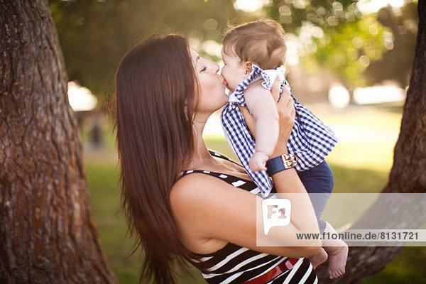 Portrait of mother kissing baby daughter