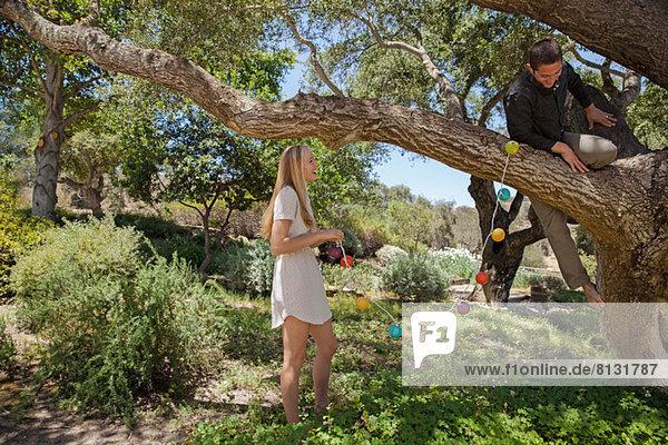 Junges Paar hängende Laternen im Baum
