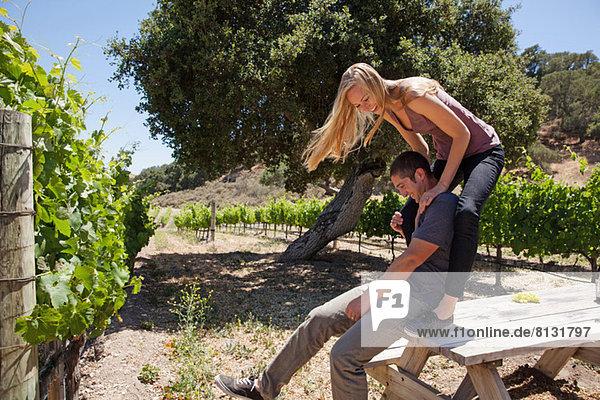 Junges Paar auf der Picknickbank im Weinberg