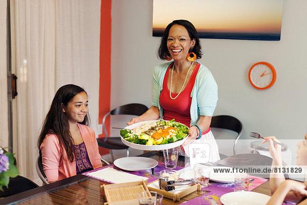 Frau serviert Gnocchi und Brokkoli Gericht