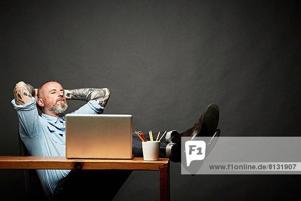Mann sitzend mit Beinen auf dem Tisch