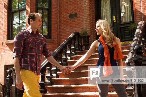 Paar geht Hand in Hand an einer Außentreppe vorbei