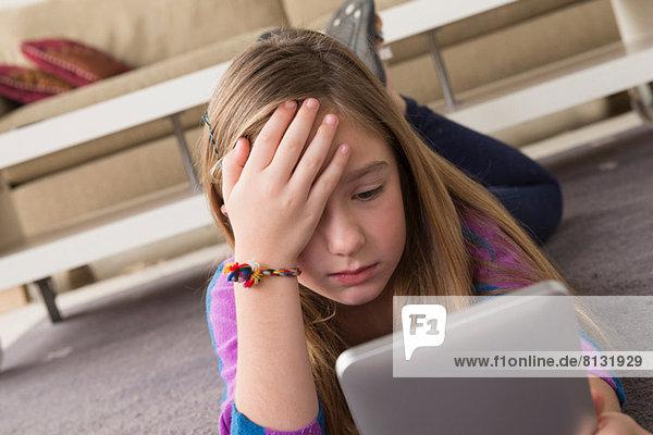 Mädchen beim Betrachten des digitalen Tabletts in Verwirrung