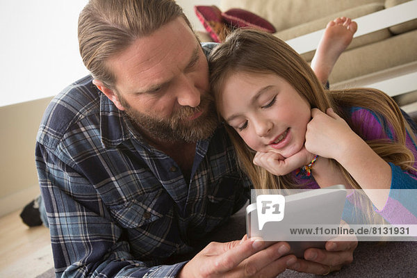 Vater und Tochter beim Betrachten des digitalen Tabletts