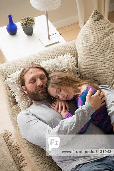 Vater und Tochter schlafen auf der Couch