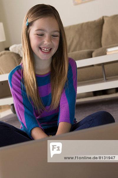 Mädchen schaut auf Laptop