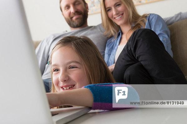 Eltern  die das Kind mit dem Laptop betrachten