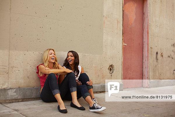 Frauen auf dem Boden sitzend lachend