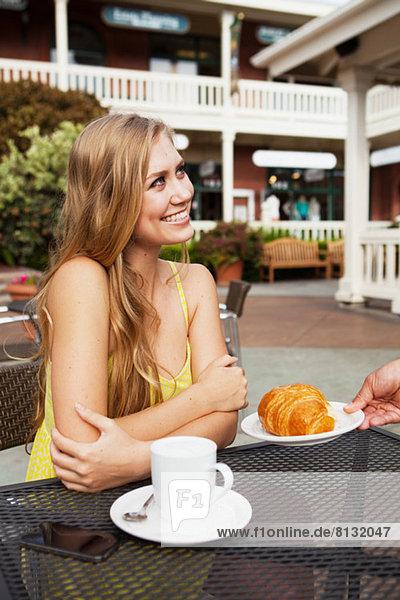 Frau wird ein Croissant serviert