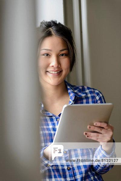 Frau mit digitalem Tablett mit Blick auf die Kamera