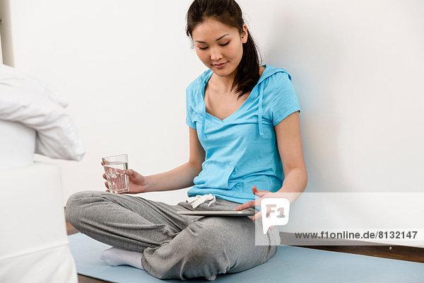 Frau sitzend im Schneidersitz auf Matte mit digitalem Tablett