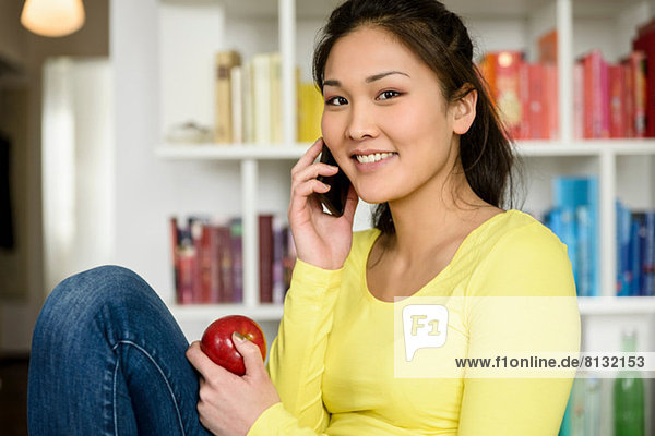 Frau mit rotem Apfel hört auf Handy