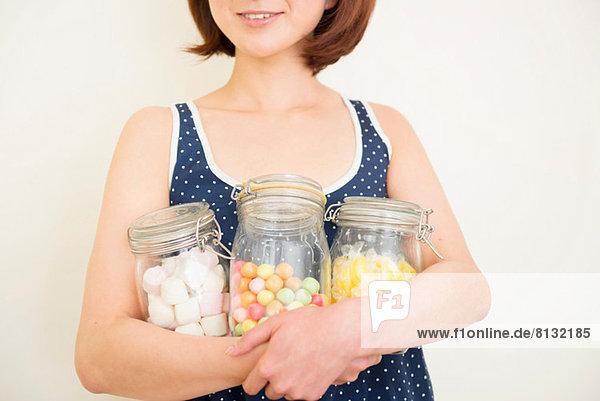 Frau umarmt drei Gläser Marshmallows  Kaugummi und Brauselimonade