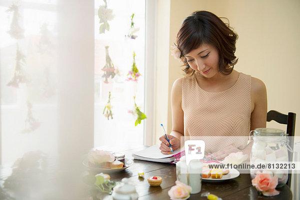 Frau beim Schreiben von Notizen zur Teezeit