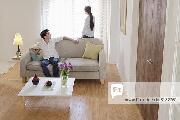 Mann dreht sich auf dem Sofa um  um seine Frau anzusehen.