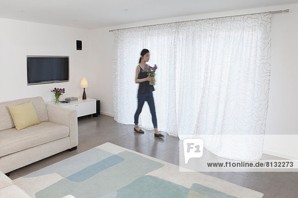 Woman with vase of flowers walking past curtains
