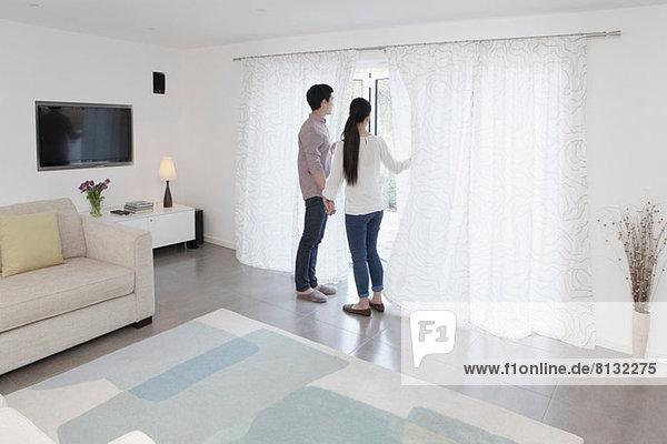 Mann und Frau schauen aus der Glastür.