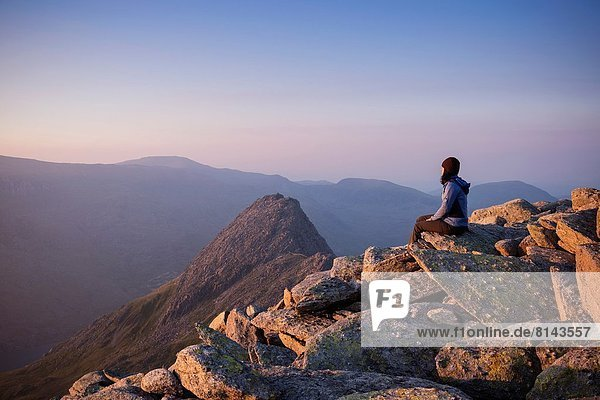 Female hiker on summit of Glyder Fach with Tryfan in background  Snowdonia national park  Wales.