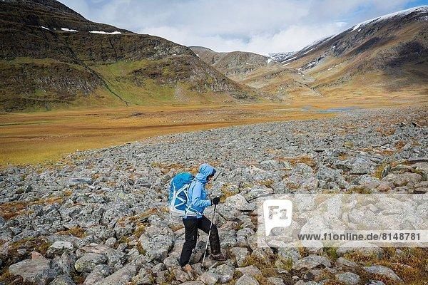 Female hiker hikes over rocky terrain in Tjäktjavagge on Kungsleden trail  Lappland  Sweden.