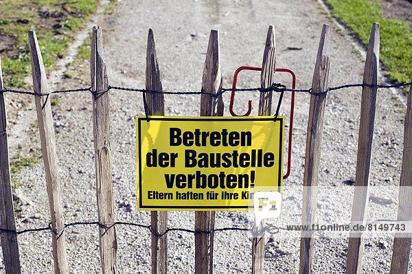 'Schild an Staketenzaun ''Betreten der Baustelle verboten'''