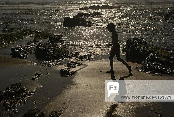 Junge läuft in der Abendsonne am Strand