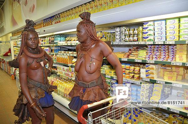 Traditionell gekleidete Himba-Frauen vor dem Kühlregal im Supermarkt