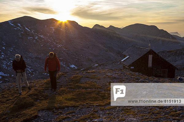 Zwei Wanderer an der Edelweißerhütte bei Sonnenuntergang Zwei Wanderer an der Edelweißerhütte bei Sonnenuntergang