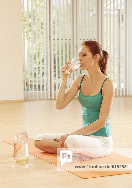 Junge Frau sitzt auf Gymnastik-Matte und trinkt Wasser aus einem Glas