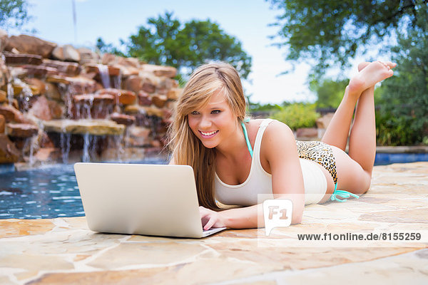 Young woman using laptop at swimming pool  smiling