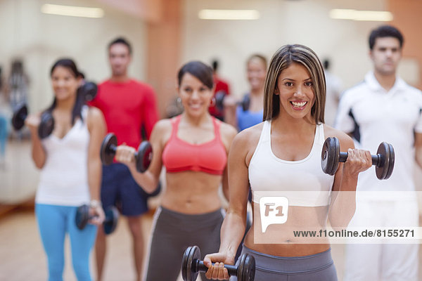 Hispanic people taking exercise class in gym