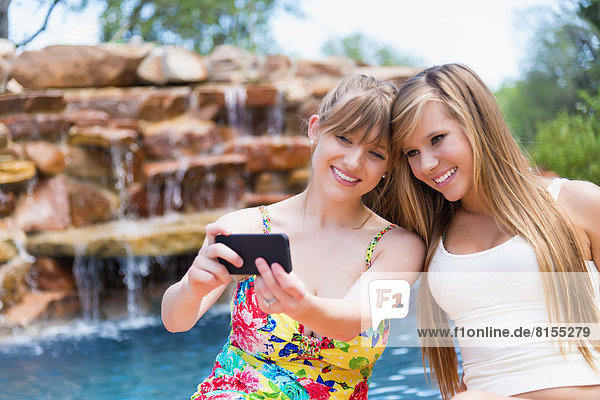 Junge Frauen  die ein Smartphone benutzen  um am Swimmingpool zu fotografieren  lächeln