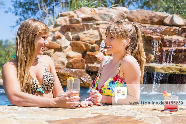Young women sitting at swimming pool  smiling