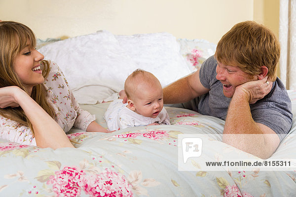 Parents with baby boy on bed  smiling