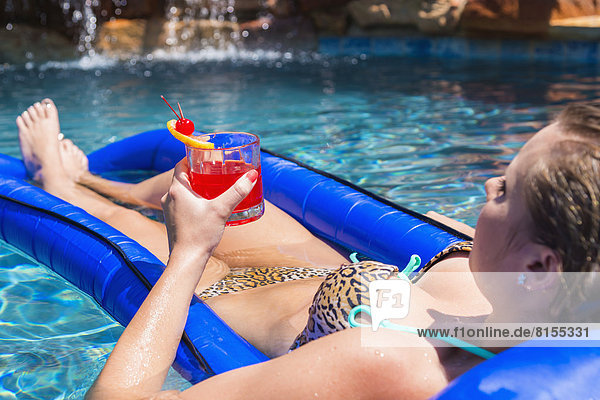 Young woman relaxing on float in swimming pool  smiling