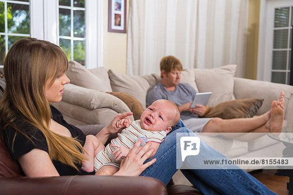 Mutter mit weinendem Sohn und Vater mit digitalem Tablett im Hintergrund