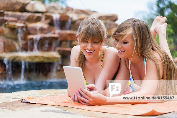 Junge Frauen  die ein digitales Tablett im Schwimmbad benutzen  lächeln