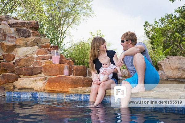Eltern mit Baby am Pool sitzend  lächelnd