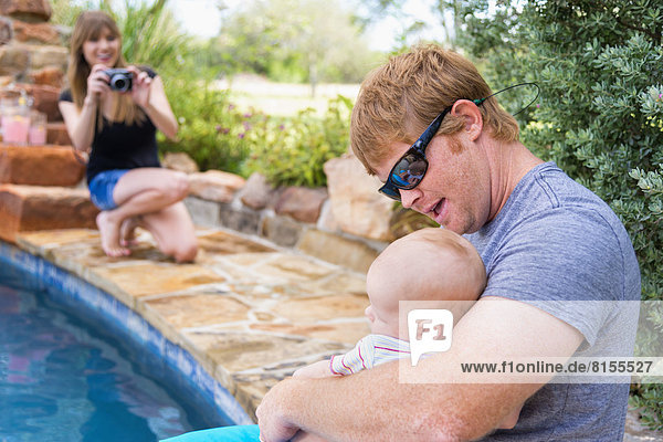 Mother taking picture of father and baby boy  smiling