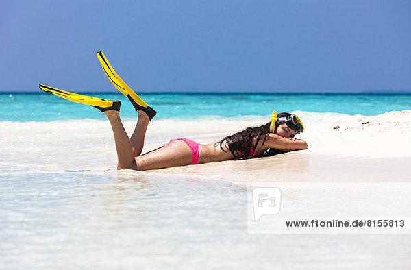 Malediven Junge Frau am Strand liegend