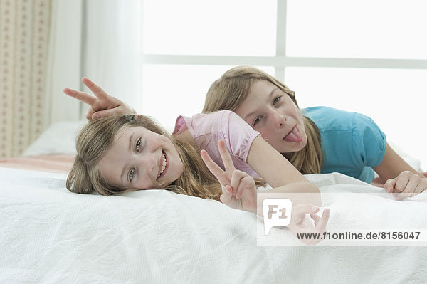 Portrait of girls lying on bed and showing V sign  smiling Portrait of girls lying on bed and showing V sign, smiling