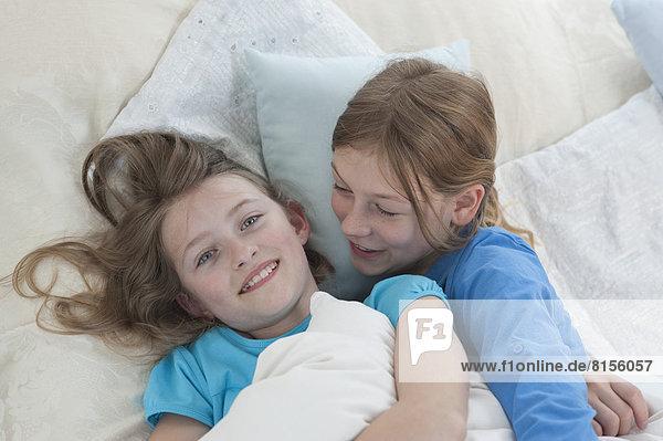 Mädchen erzählen Geheimnisse im Bett  lächelnd