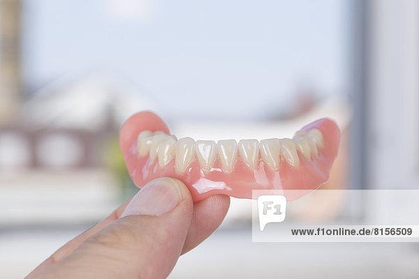 Deutschland  Freiburg  Zahntechniker mit Zahnersatz in der Hand