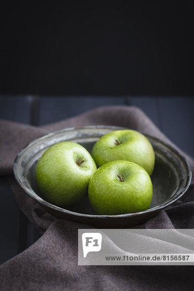 Schale mit grünen Äpfeln auf Holztisch  Nahaufnahme