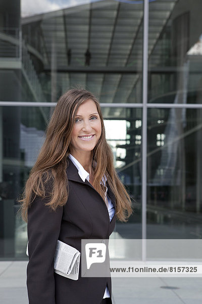 Porträt einer Geschäftsfrau  die Zeitung hält  lächelnd