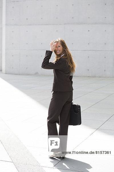 Geschäftsfrau mit Aktentasche  lächelnd